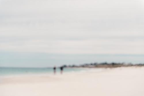 Blurred image of two people walking on a beach in summer