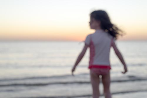 Blurred view of a young girl standing in the ocean at sunset