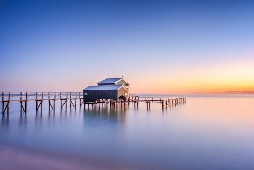 Boathouse on a beach at sunrise