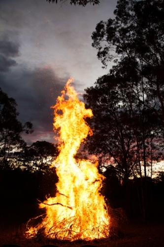 Bonfire burning high and bright in a paddock at sunset