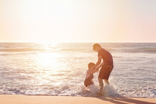 Boy and Toddler Jumping in the Waves on a Beach at Sunset