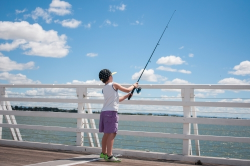Boy fishing on a pier