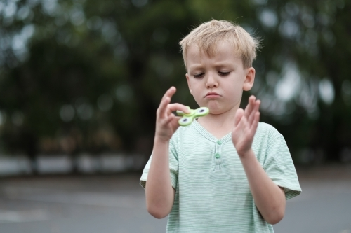 Boy frowning playing with fidget spinner toy