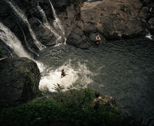 Boy jumping off a waterfall