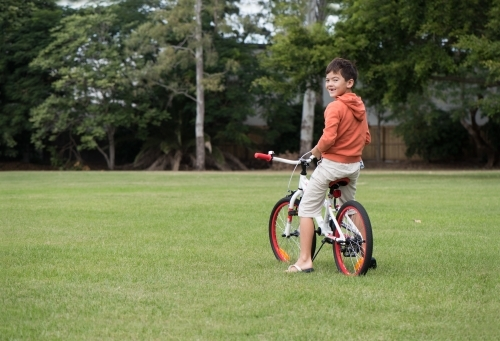 Boy riding orange bicycle on lawn.