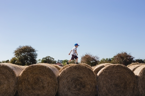 Boy running over the top of hay bales
