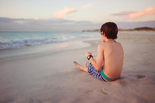 Boy sitting on a beach blowing bubbles on a warm summer evening