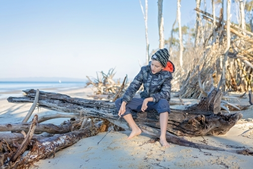 Boy sitting on log on remote beach in Queensland