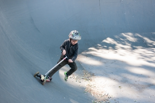 Boy skating in a skate park ramp on scooter