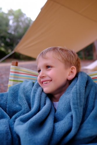Boy smiling, sitting outside tent in camping chair