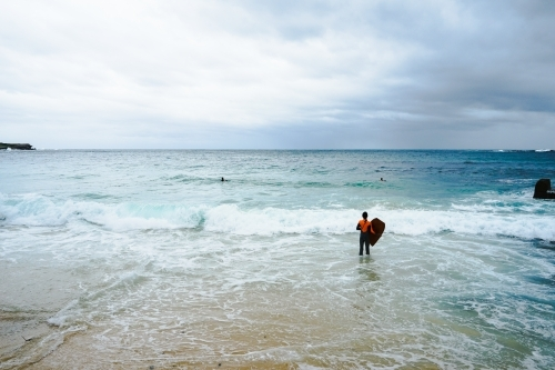 Boy standing at beach with bodyboard