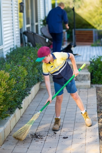 Boy sweeping path with raw broom