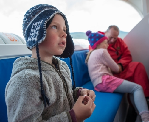 Boy travelling on a boat in cold weather