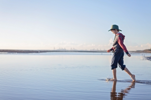 Boy walks on the beach at lowtide in winter barefoot