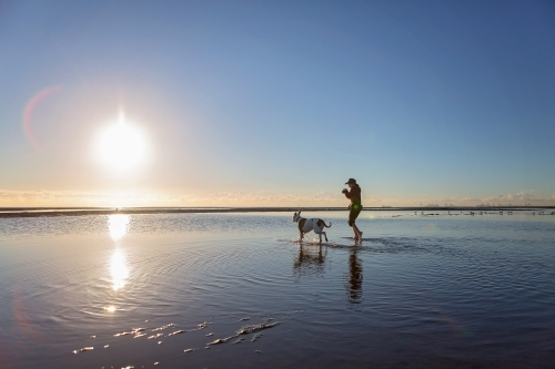 Boy walks on the beach at lowtide in winter barefoot with his dog