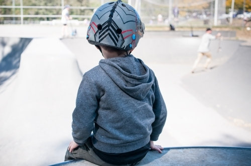 Boy with helmet watching skaters in a skate park