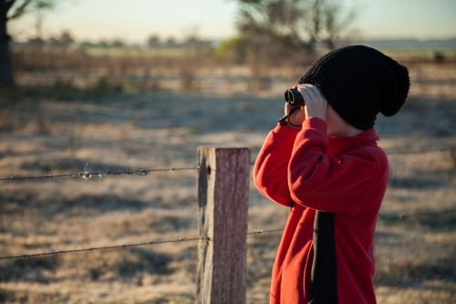 Young boy bird watching on cold winter morning