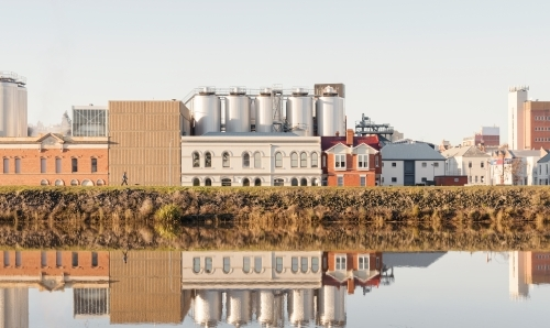 Brewery building on the side of the Tamar River, the building is reflected on the rivers surface