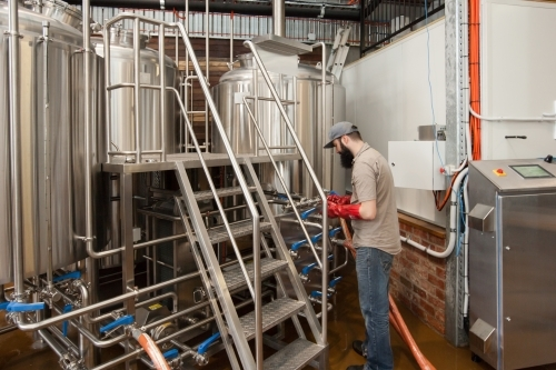 Brewer changing lines at a microbrewery