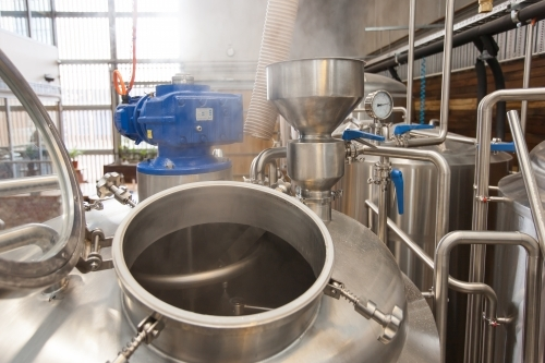 Steam escaping from hatch of a stainless steel tank at a microbrewery