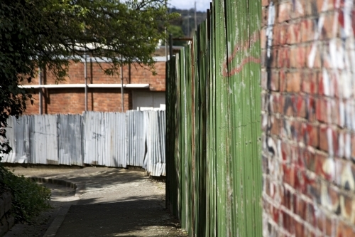 Laneway with brick and corrugated iron fence