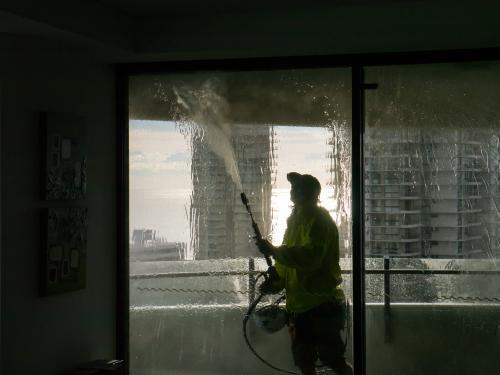 Worker using a pressure hose to clean the windows of an apartment building