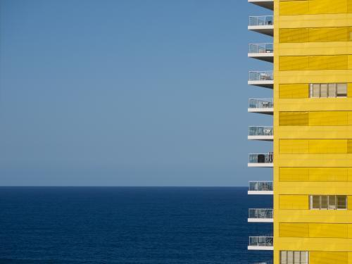 Yellow apartment building with blue sky and sea