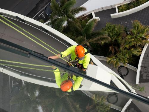 Window cleaner abseiling down a tall building on the Gold Coast