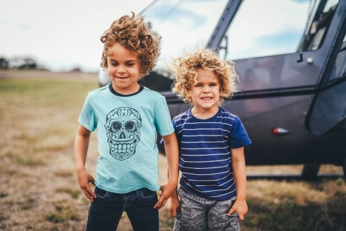 Brothers in front of a helicopter