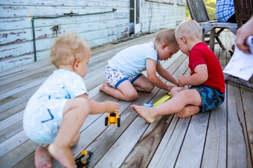 Brothers play with toys on patio deck of weather farm house.