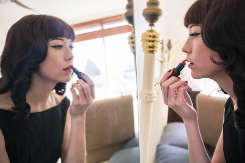 Brunette woman applying red lipstick in preparation for a formal event