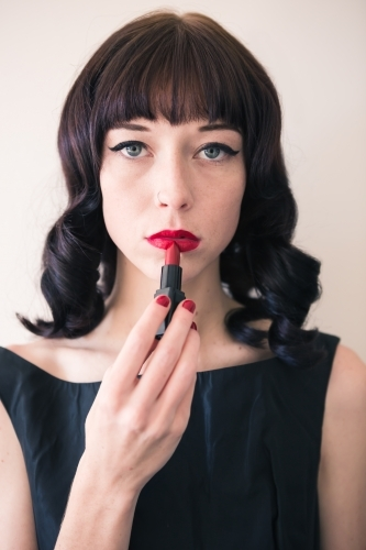 Brunette woman holding red lipstick to her lips staring into camera