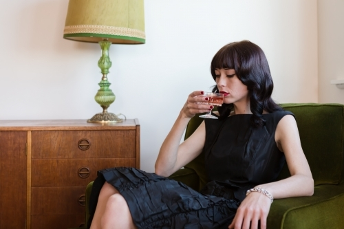 Brunette woman sipping pink champagne in a retro living room