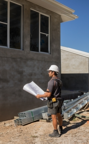 Builder with hard hat & tool belt holding plans outside new house construction