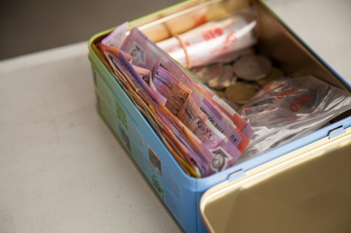 Tin box of money in notes and coins