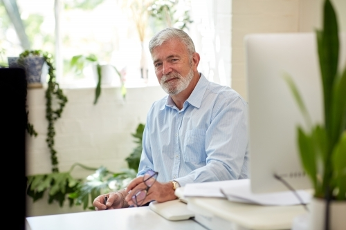 Businessman sitting at a desk in an open office studio