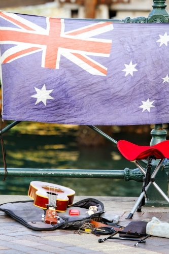 A busker's guitar and stool in front of the Australian Flag
