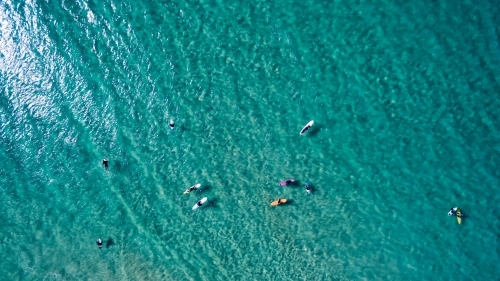 Aerial view of eleven surfers waiting for waves.