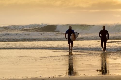An old and young man walking into the surf with surfboards.