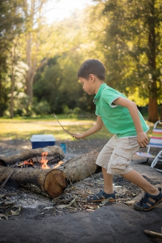 6 year old mixed race boy throws a stick on a camp fire
