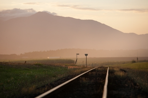 Late afternoon light on cane train tracks with mountains in background