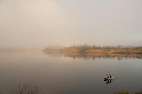 Fishermen in a tinny on a misty lake