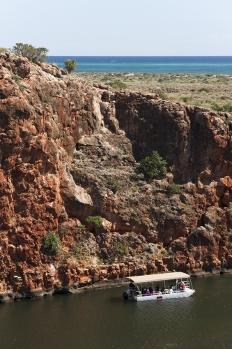 Looking down from cliff to tourist boat in remote gorge