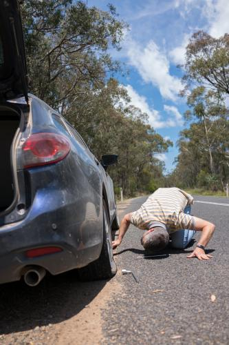 Man changes a tyre after getting a flat tyre on a country road