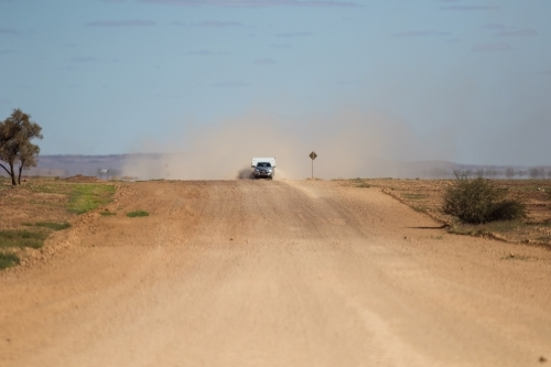 Car and caravan being driven along a wide outback road