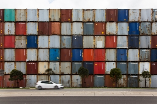 Car in front of colourful shipping containers