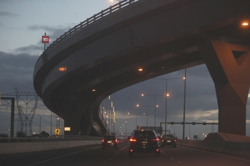 Cars passing under a bridge on Melbourne City roads in the evening