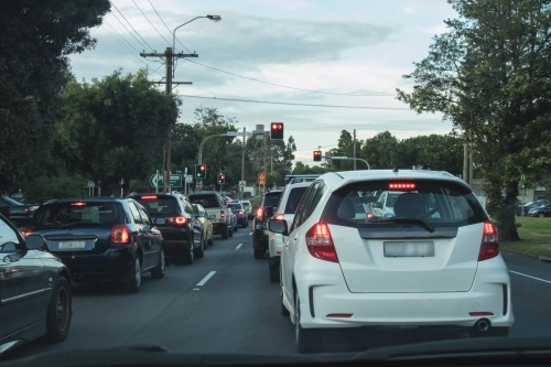 Cars stopped at red traffic light in urban peak traffic