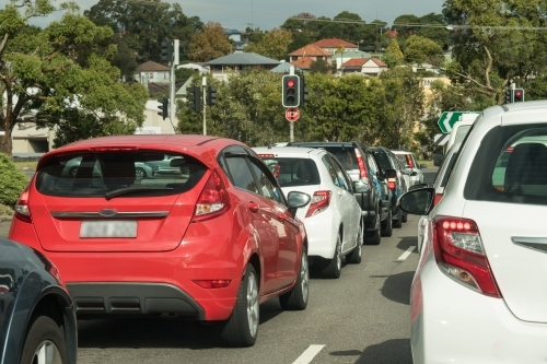 Cars stopped at red traffic lights in urban traffic in daylight