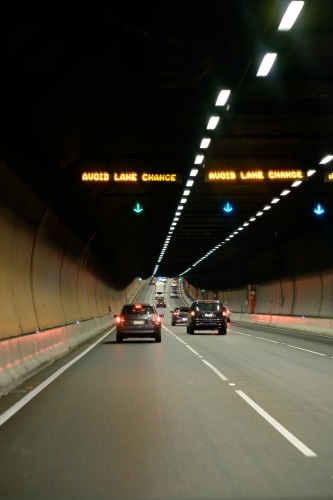 Cars travelling through city toll road underground tunnel
